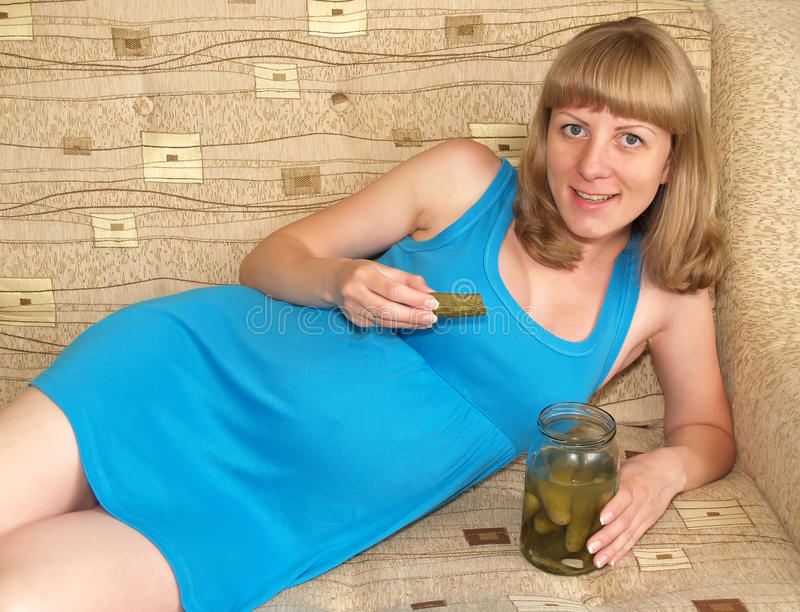 The pregnant woman eats pickle, lying on a sofa. Toxicosis royalty free stock images