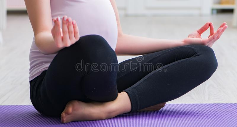 Pregnant woman exercising in anticipation of child birth. The pregnant woman exercising in anticipation of child birth royalty free stock photos