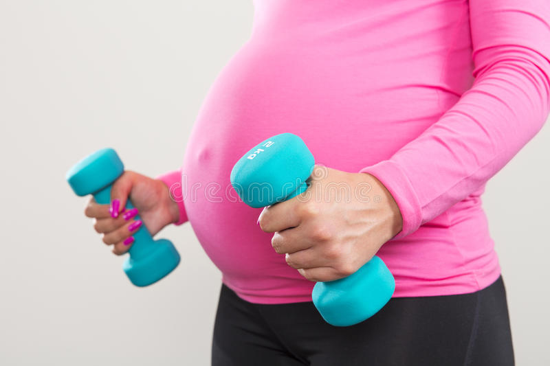 Pregnant woman exercising with training weights royalty free stock photo