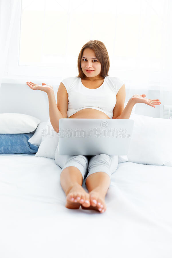 Pregnant Woman feels Confused While Using her Laptop Computer royalty free stock photos