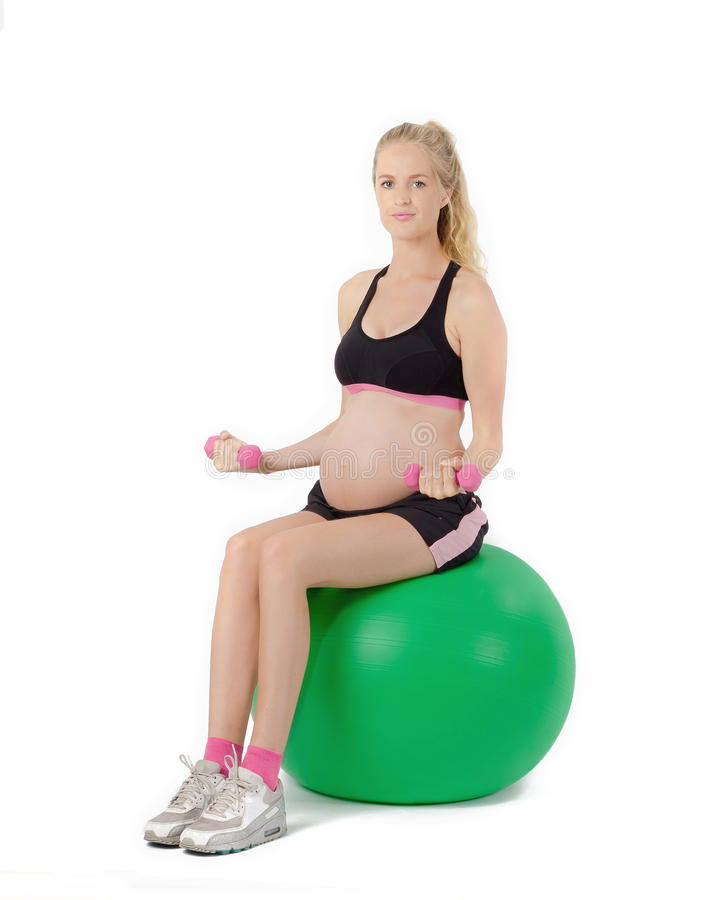 Pregnant Woman Fitness. Bicep Curl Exercise. Pregnant woman sitting on yoga ball performing bicep curl with weights stock photos