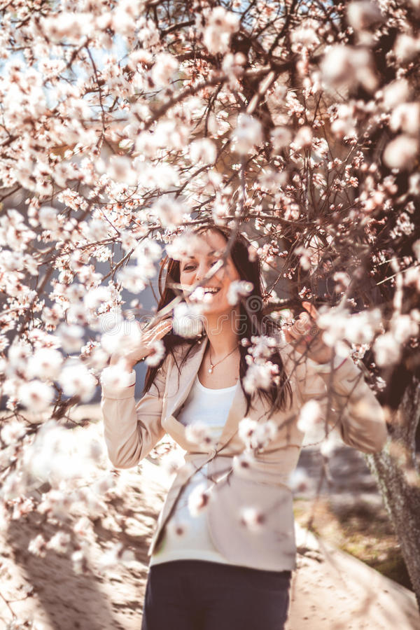 Pregnant woman in the flowering branches stock image