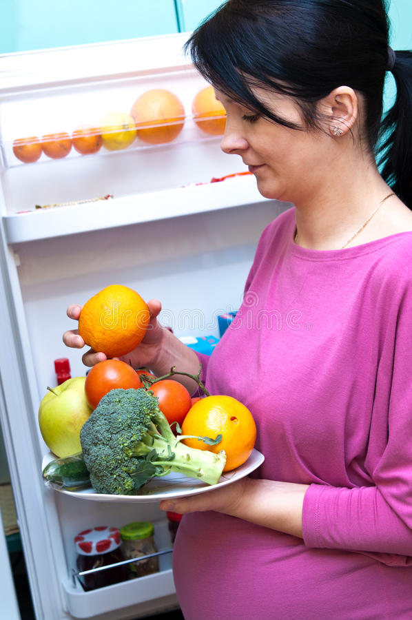 Pregnant woman with food. A pregnant woman making healthy food choices from the fridge royalty free stock photo