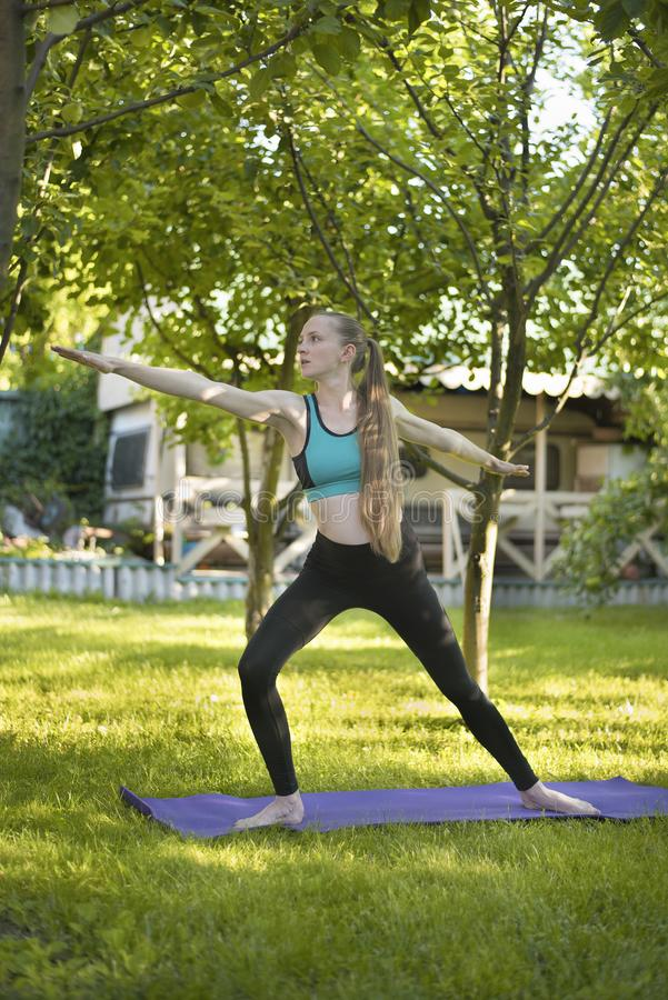 Pregnant woman in the garden practices yoga. Warrior`s pose. Sum stock photography