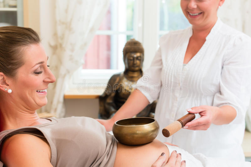 Pregnant woman getting sound bowl treatment royalty free stock photography