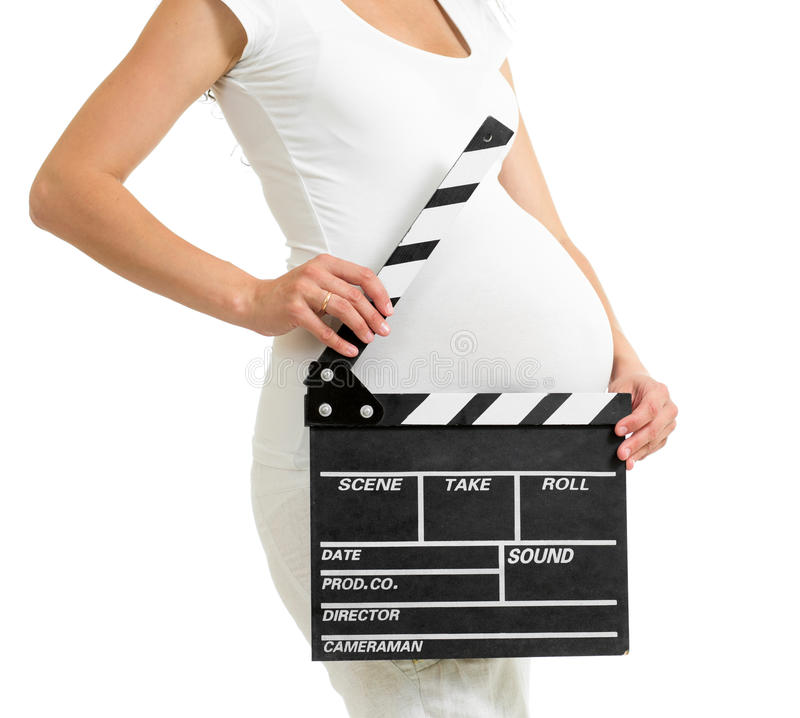 Pregnant woman hands holding clapper board on her belly. Isolated royalty free stock photography