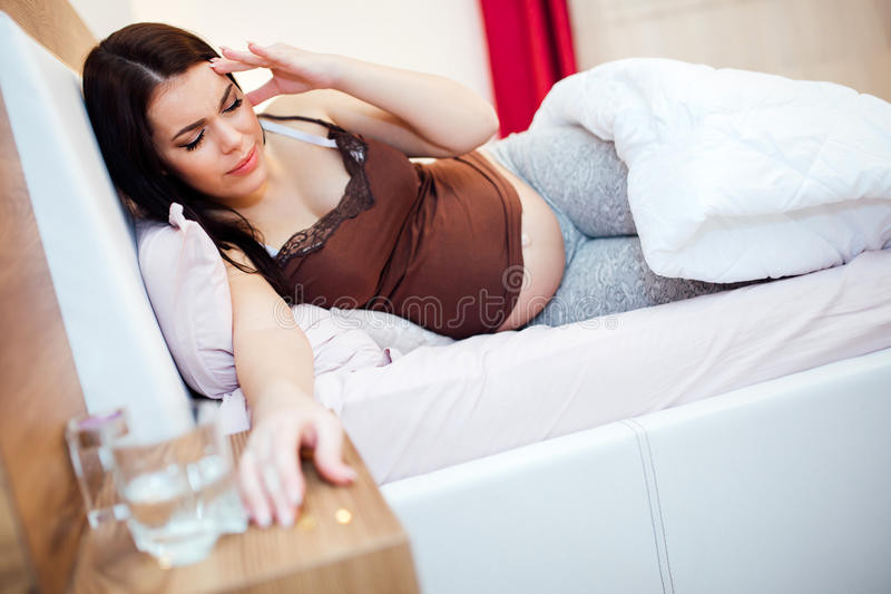 Pregnant woman having a bad headache. Pregnant woman having a bad migrane but certain pills are allowed during pregnancy stock photography