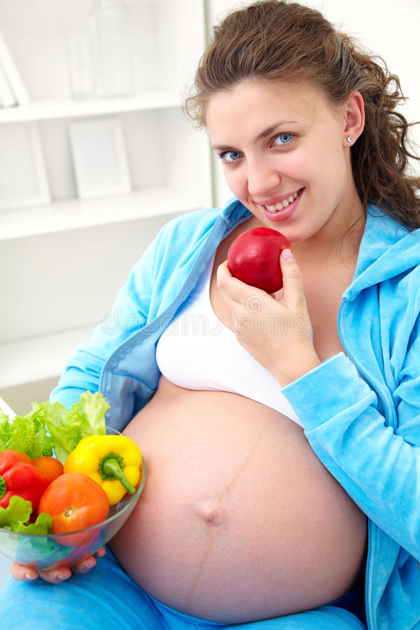 Pregnant woman and healthy food. Pregnant woman with healthy food at home background royalty free stock photography