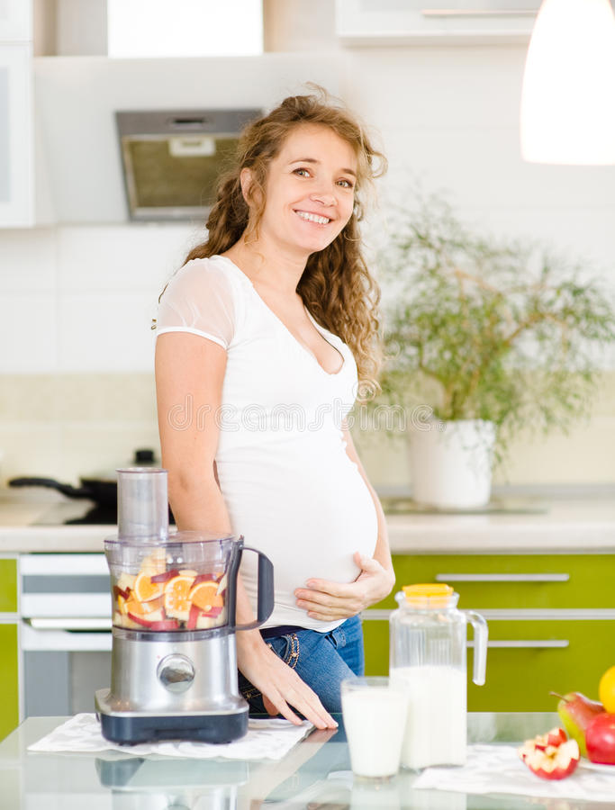 Pregnant woman with healthy food. In kitchen royalty free stock photography