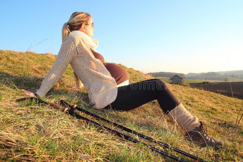 Pregnant woman heaving a break during a walk. A Pregnant woman heaving a break during a walk stock photography