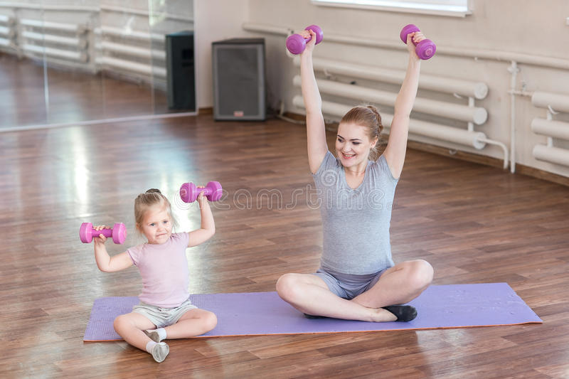 Pregnant woman with her daughter doing gymnastics royalty free stock images