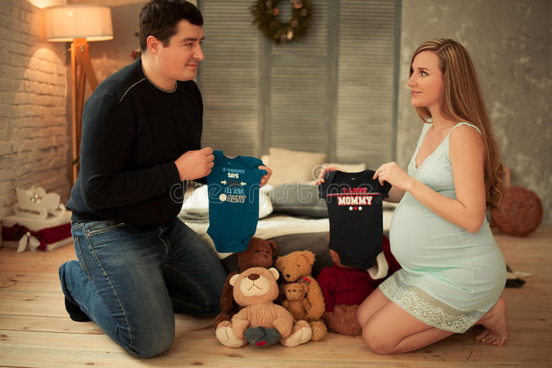 Pregnant woman with her husband chooses clothes for future baby. royalty free stock photography
