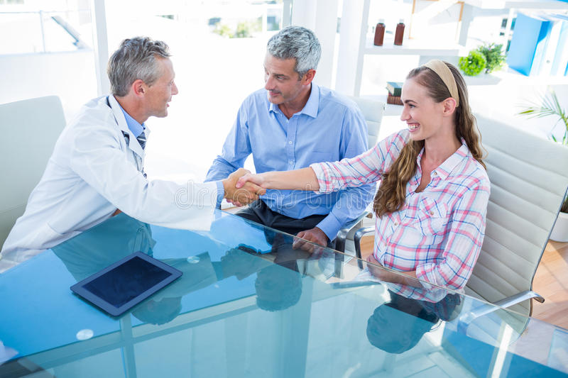 Pregnant woman and her husband discussing with doctor. Pregnant women and her husband discussing with doctor in clinic royalty free stock photo