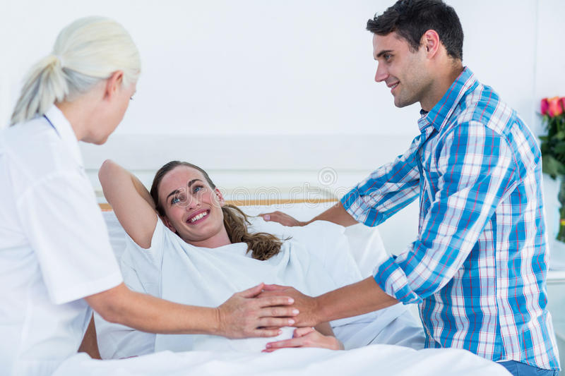 Pregnant woman and her husband having a doctor visit stock photography
