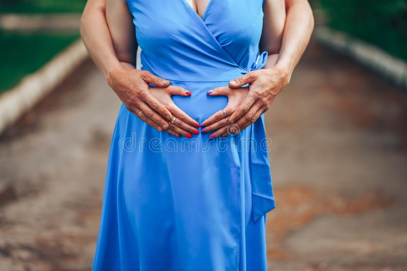 Pregnant woman and her husband holding hands on tummy in heart shape. Young loving family. New life concept stock image
