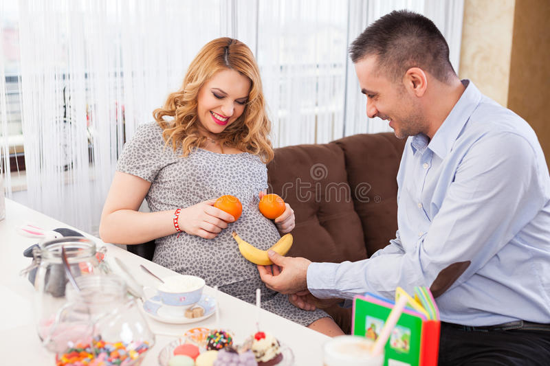 Pregnant woman and her husband. Picture of a young pregnant women and her husband making a smile on her belly with a banana and two oranges, sitting at the royalty free stock image