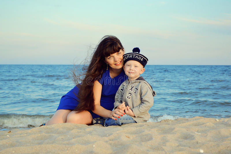 Pregnant woman with her son on the beach. Pregnant women with her son on the beach. The boy on the cap is written in Russian Captain royalty free stock photography