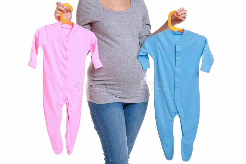 Pregnant woman holding baby clothes. royalty free stock images
