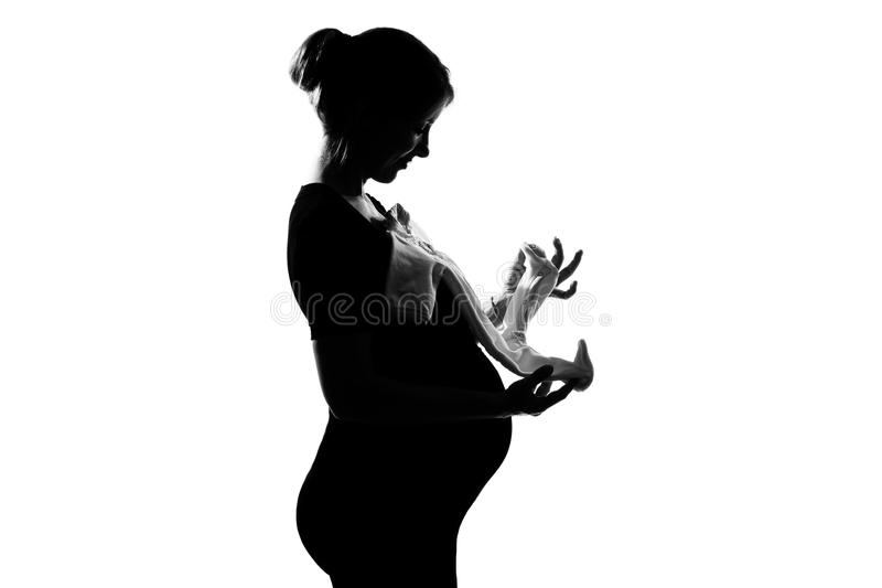 Pregnant woman holding baby clothes royalty free stock photo