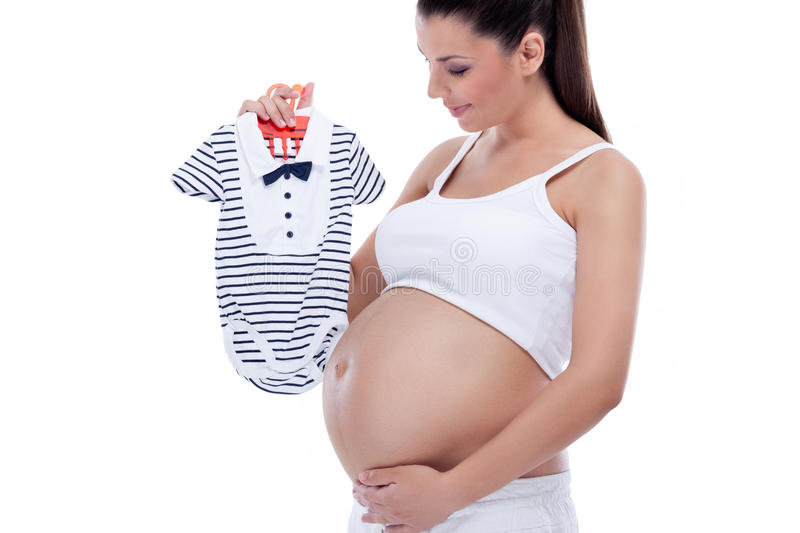 Pregnant woman holding baby clothes. Young beautiful pregnant woman holding baby clothes royalty free stock photos