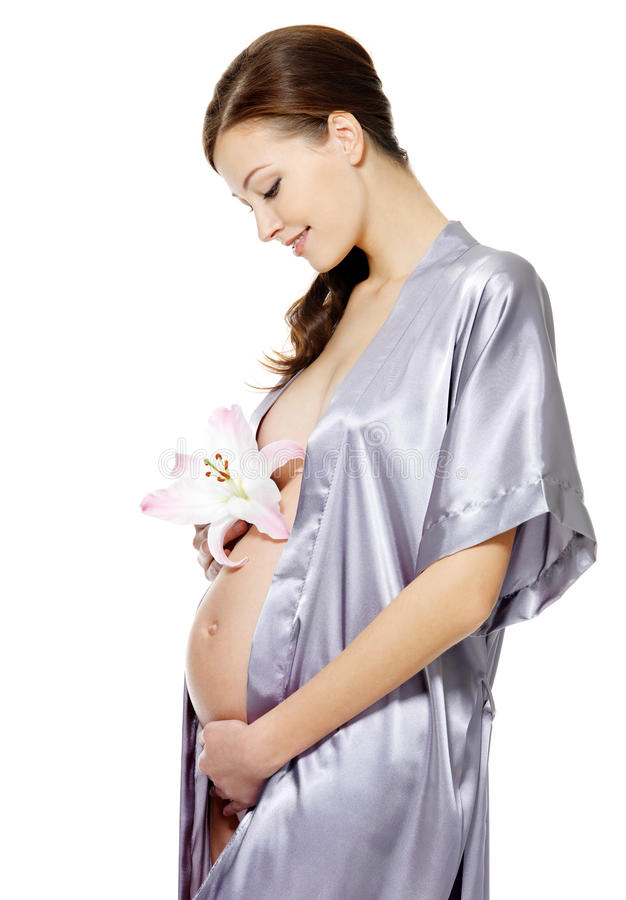 Pregnant woman holding belly and flower royalty free stock images