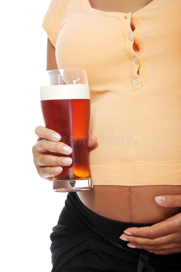 Pregnant woman holding a glass of alcohol. Pregnant woman holding a glass alcohol next to her belly, over a white backgroung stock photography