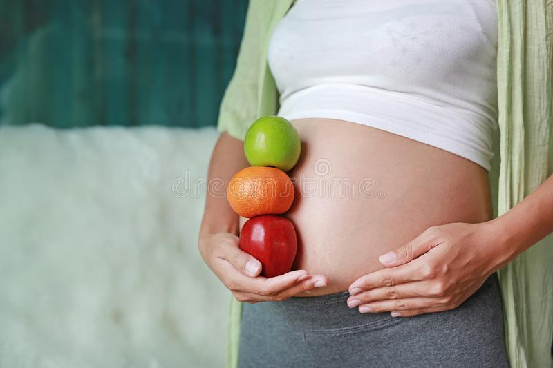 Pregnant woman holding Green-Red Apple and Orange fruit at her tummy. Dieting Concept royalty free stock photos