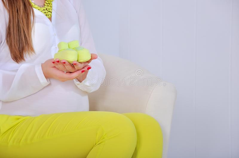 Pregnant woman holding small baby shoes royalty free stock photo