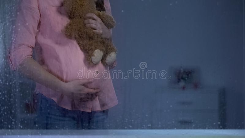 Pregnant woman hugging teddy bear behind rainy window, baby expectation, care stock image