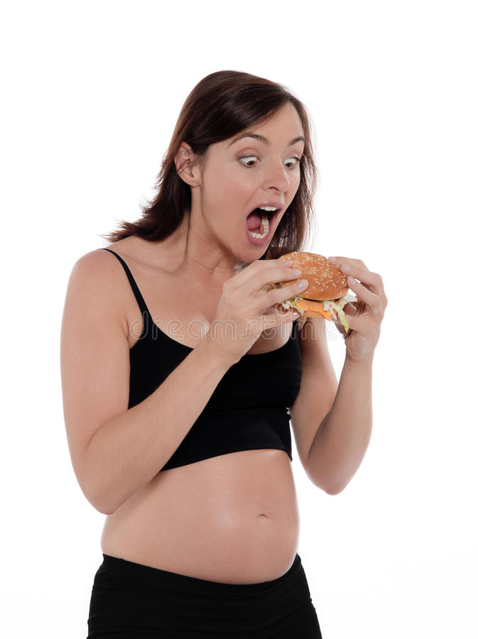 Pregnant Woman Hungry. Pregnant caucasian woman hungry eat hamburger isolated studio on white background stock photos
