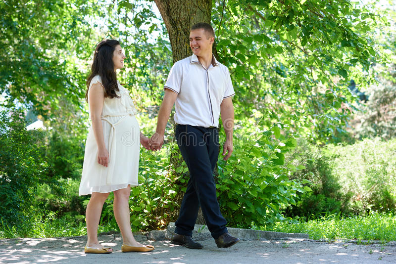 Pregnant woman with husband walking in the city park, family portrait, summer season, green grass and trees. Pregnant women with husband walking in the city park royalty free stock photo