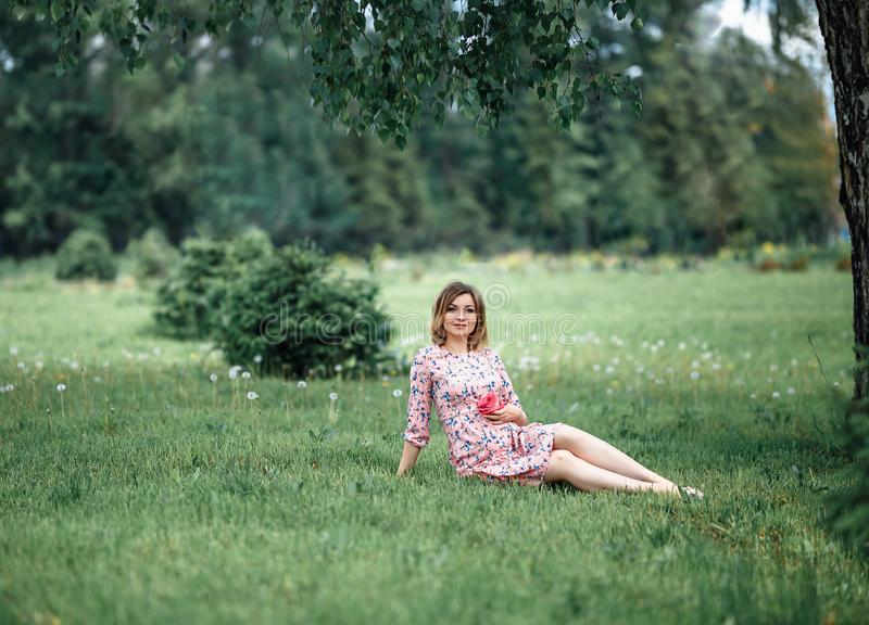 Pregnant woman inpink dress sitting on grass and touching bump whilst holding pink rose girl waiting.  royalty free stock photos
