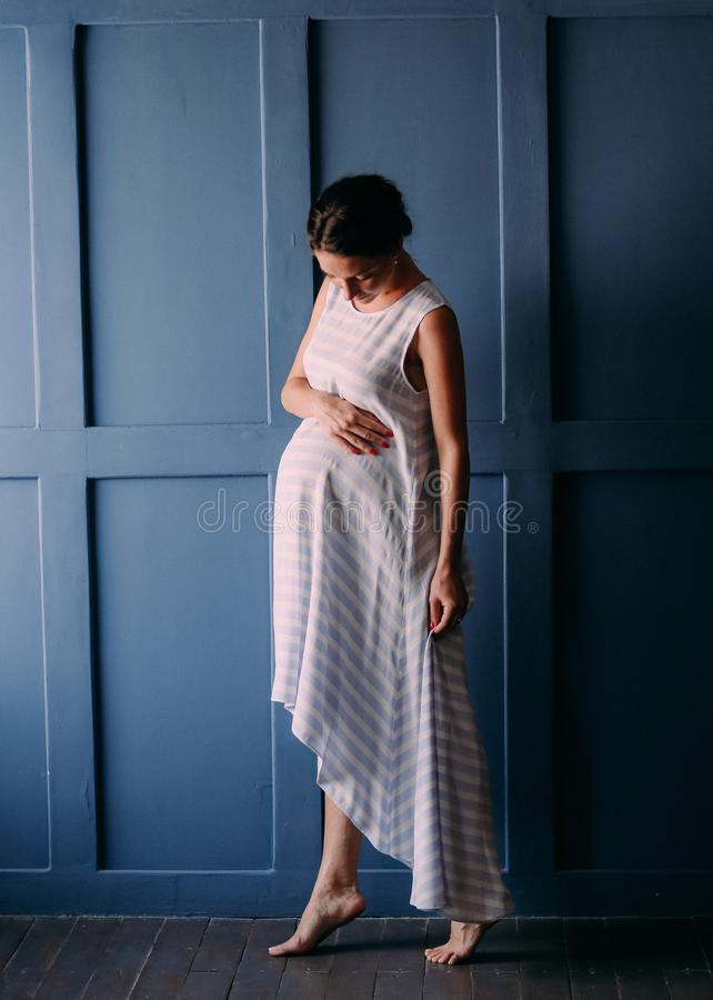 Pregnant woman inside room gently strokes belly stock images