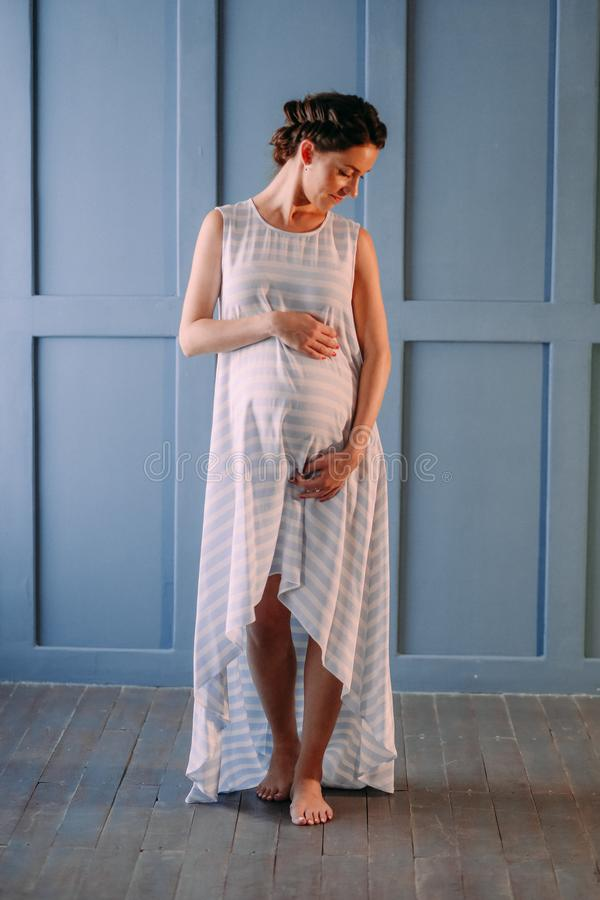 Pregnant woman inside room gently strokes belly royalty free stock images