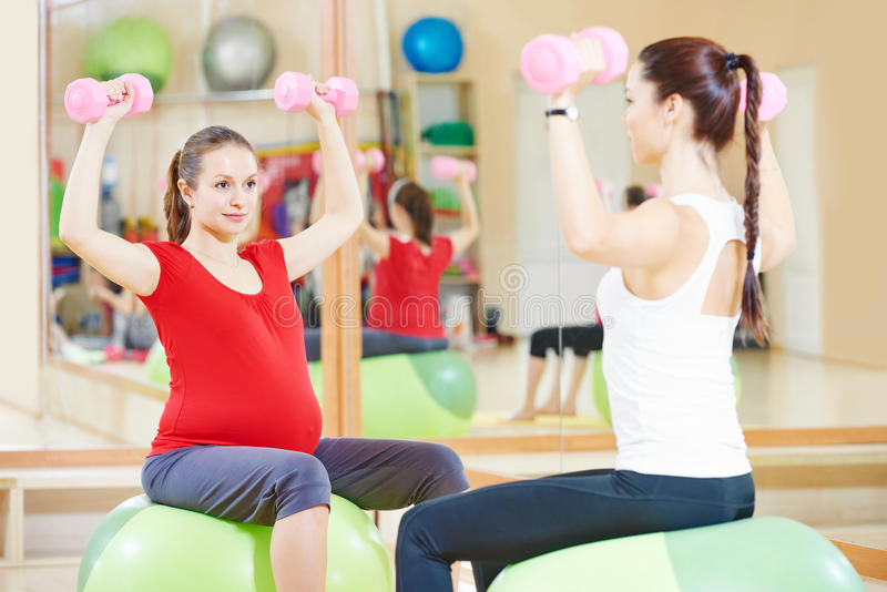 Pregnant woman with instructor doing fitness ball exercise royalty free stock photo