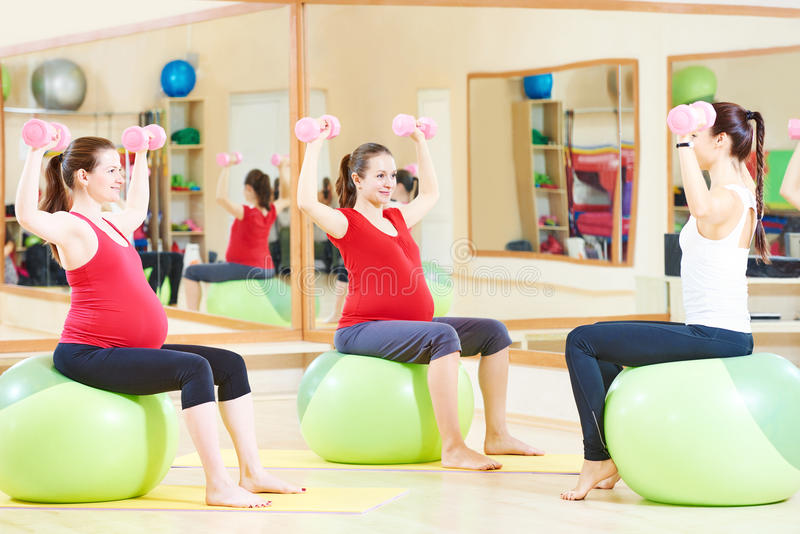 Pregnant woman with instructor doing fitness ball exercise stock images
