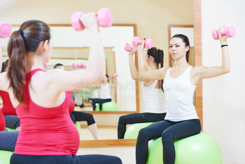 Pregnant woman with instructor doing fitness ball exercise royalty free stock images