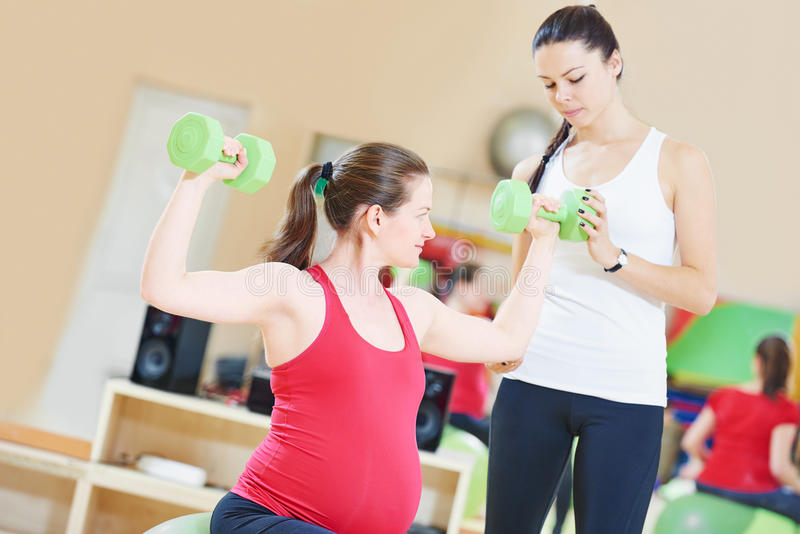 Pregnant woman with instructor doing fitness ball exercise royalty free stock image