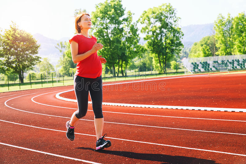 Pregnant woman jogging on running track in stadium. Pregnant sporty fitness woman jogging on red running track in stadium. Training summer outdoors on running stock photo