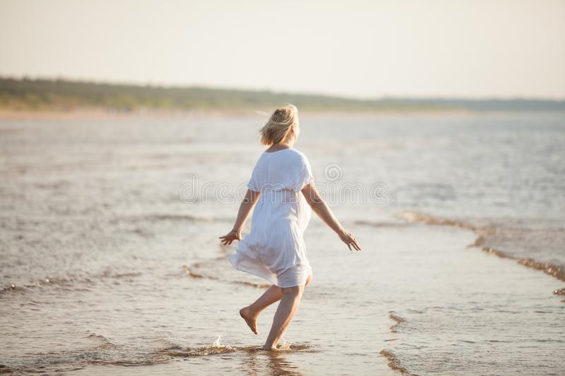Pregnant woman jumping on the beach. Cheerful woman running on the seashore on her pregnancy at summer evening royalty free stock image