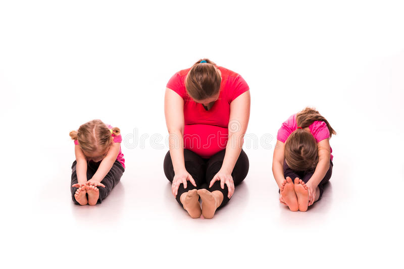 Pregnant woman with kids exercising isolated. Pregnant women doing gymnastic exercises with kids isolated over white background, active and sportive pregnancy stock images