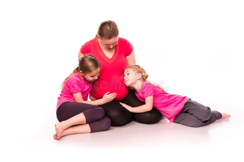 Pregnant woman with kids exercising. Pregnant women doing gymnastic exercises with kids over white background, active and sportive pregnancy, healthy motherhood stock images
