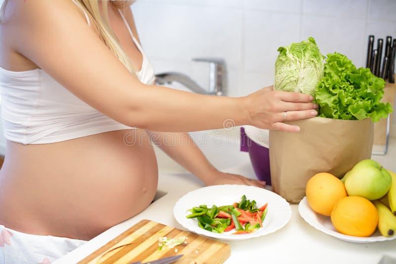 Pregnant woman at kitchen preparing salad, close up royalty free stock photography