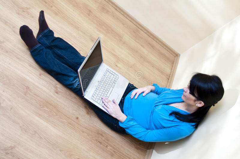 Pregnant woman and laptop. Pregnant woman with her laptop at home stock images
