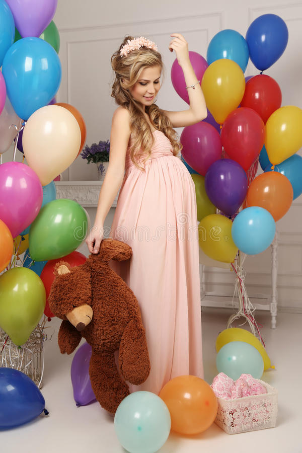 Pregnant woman with long blond hair in elegant dress, with a lot of colorful air balloons. Fashion interior photo of beautiful pregnant woman with long blond royalty free stock image