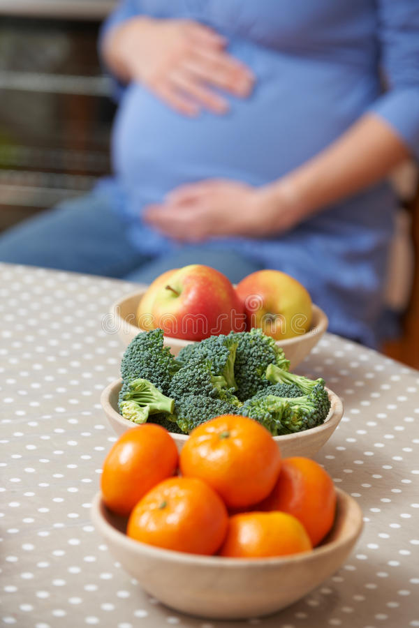 Download Pregnant Woman Looking At Bowls Of Healthy Fruit And Vegetables Stock Photo - Image of vertical, caucasian: 63229390