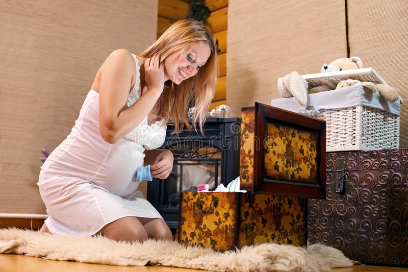 Pregnant Woman Looking Into Case With Baby Clothes Stock Photos