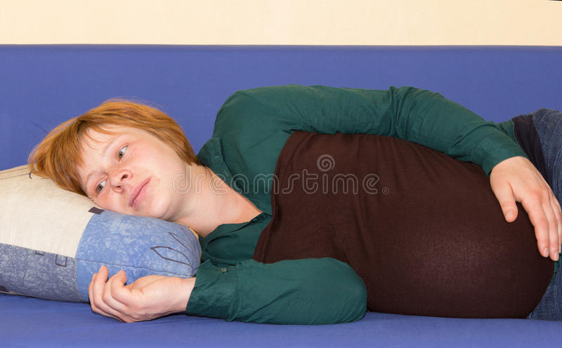 Pregnant woman lying on a sofa thinking royalty free stock image