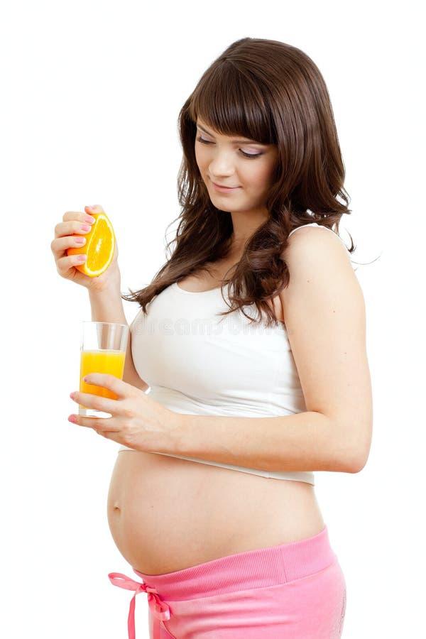 Pregnant woman making fresh orange juice royalty free stock image