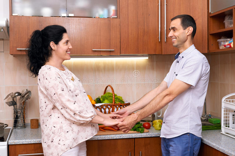 Pregnant woman and man in kitchen interior with fresh fruits and vegetables, healthy food concept, happy couple royalty free stock photo